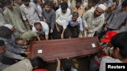 Relatives and colleagues carry the casket of Pakistani journalist Salim Shahzad for burial in Karachi in June 2011.