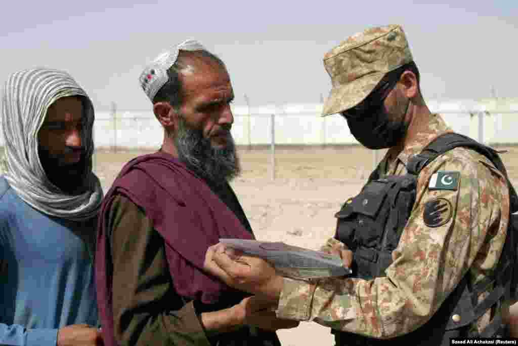 Пакистански војник ги проверува документите на луѓе кои пристигнуваат од Авганистан на преминот Пријателство во Чаман на 27 август.