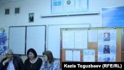 Кезектен тыс президент сайлауы кандидаттары суреттері ілінген тақтаның қасында отырған адамдар. Aлматы, 8 сәуір 2015 жыл. (Көрнекі сурет).