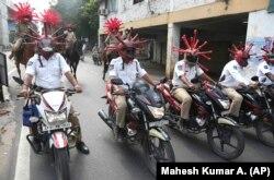 Індійська поліція з шоломах із символічними бацилами коронавірусу під час акції привернення уваги до потреби карантину. Індія, Гайдарабад, квітень 2020 року
