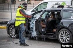 Мужчына ачышчае таксі ў цэнтры Стакгольма, каб не дапусьціць распаўсюджваньня COVID-19