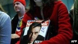 Сторонница Майка Хакаби держит журнал Newsweek c его автографом