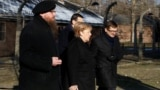 "POLAND -- German Chancellor Angela Merkel, Polish Prime Minister Mateusz Morawiecki and museum director Piotr Cywinski walk past the ""Arbeit Macht Frei"" gate at the former Nazi German concentration and extermination camp Auschwitz in Oswiecim, December 6"