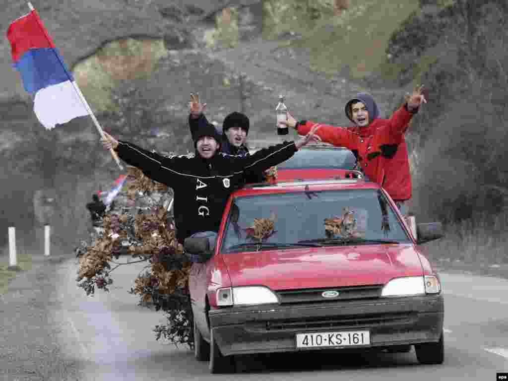 Kosovo Serbs in the town of Gracanica wave Serbian flags and carry oak branches, a traditional Christmas symbol.