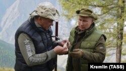 Владимир Путин передает Сергею Шойгу найденный гриб. Пока что не президентский пост. День рождения президента РФ в сибирской тайге 7 октября 2019 года
