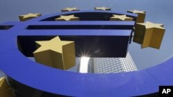 Germany -- The sun is reflected on the facade of the European Central Bank ECB Tower, seen through the Euro symbol, in Frankfurt, 06Aug2009