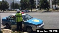 Сотрудник полиции у полицейского автомобиля.