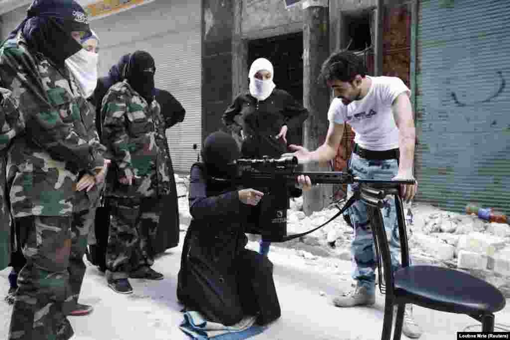 "Members of the ""Mother Aisha"" battalion, an all-female unit with the Syrian rebels, receive instruction in Aleppo's Salaheddine district. (Reuters/Loubna Mrie)"
