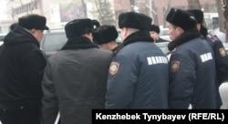 Полицейские стоят перед Национальным пресс-клубом в момент когда оппозиционным политикам вручают повестки в административный суд. Алматы, 30 января 2012 года.