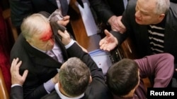 Ukrainian pro-government lawmaker Vladimir Malyshev is hurt during scuffles in parliament over an antiprotest law and other controversial legislation, which was passed on January 16.