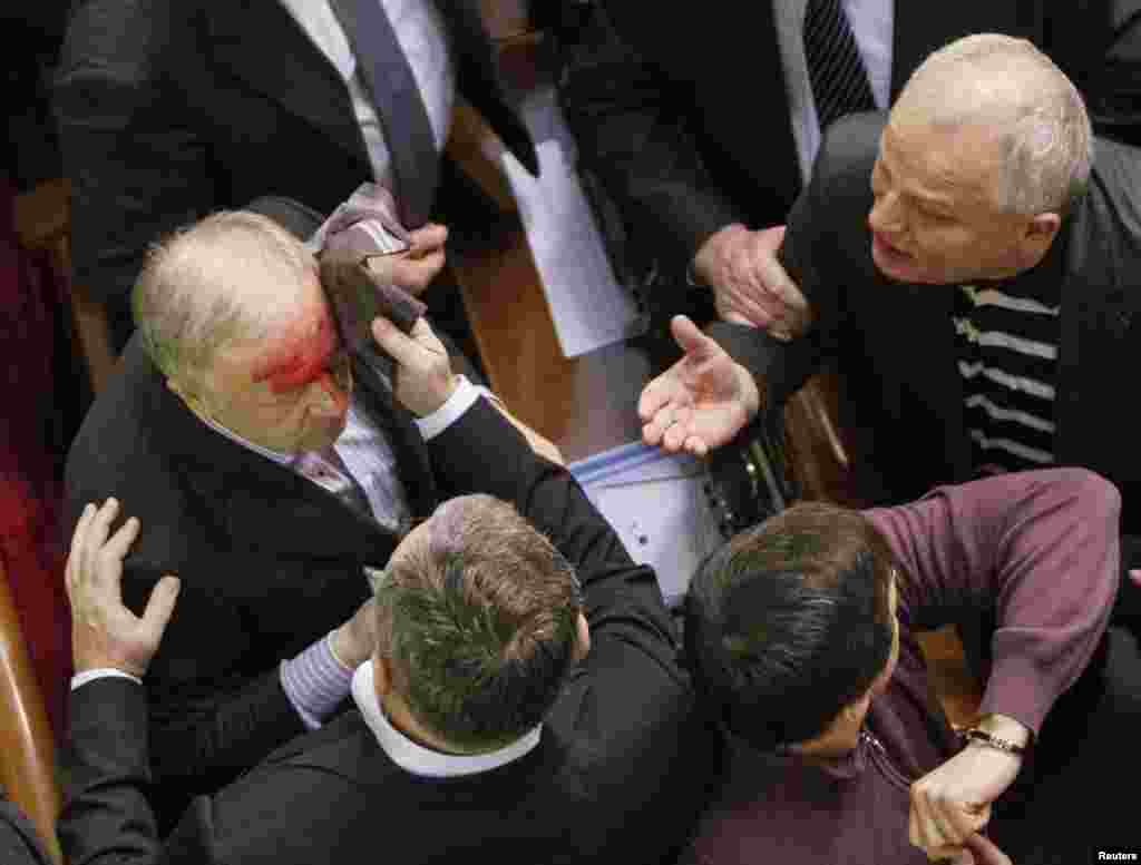 Ukrainian pro-government lawmaker Vladimir Malyshev is hurt during scuffles in parliament over an antiprotest law and other controversial legislation, which was passed on January 16. (Reuters/Gleb Garanich)