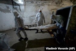 Pathologists in protective suits transport the body of a person who died of COVID-19 at a hospital morgue in Bishkek.
