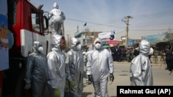 Volunteers in protective suits disinfect public areas in the capital Kabul to help in curbing the spread of the coronavirus infections on April 8.
