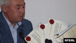 Сейтказы Матаев, председатель Союза журналистов, показывает дипломы, выписанные противникам свободы прессы в Казахстане. Алматы, 4 мая 2010 года.