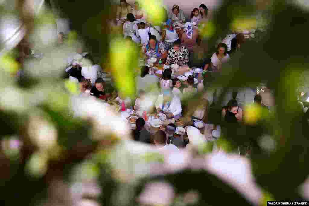 Гости за свадебным застольем на открытом воздухе