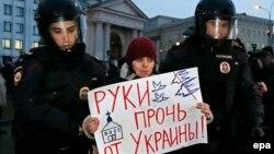 Полицейские задерживают участника антивоенного марша в Москве. 4 марта 2014 года.