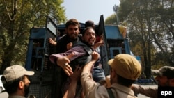 Supporter of an independent Kashmir lawmaker, Abdul Rashid Sheikh shout slogans from an Indian Police vehicle after they were detained during a protest march in Srinagar, the summer capital of Indian Kashmir, on September 26.
