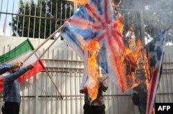 Iran -- İranlı kişi ABŞ, Britaniya və İsrail bayraqlarını yandırır, 2 sentyab 2015