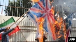 Iranians burn U.S., British, and Israeli flags at the inauguration of an anti-U.S. panel on the wall of the former U.S. Embassy in Tehran on September 2, 2015.