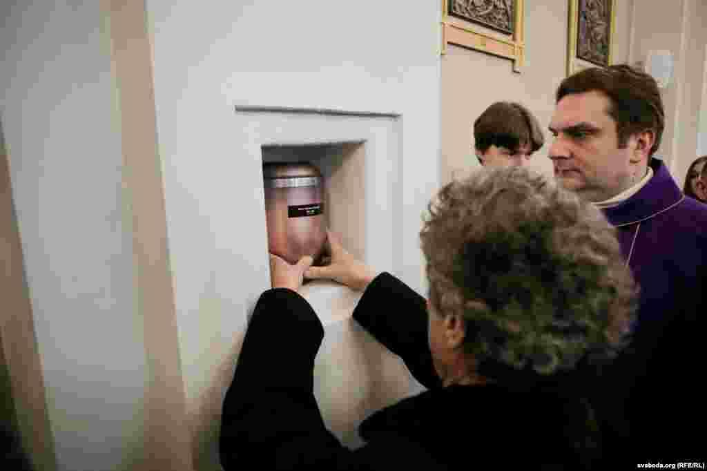 Адам Замойскі зьмяшчае ўрну з прахам у нішу касьцёла. Справа — Юры Санько, пробашч касьцёла Сьвятога Роха