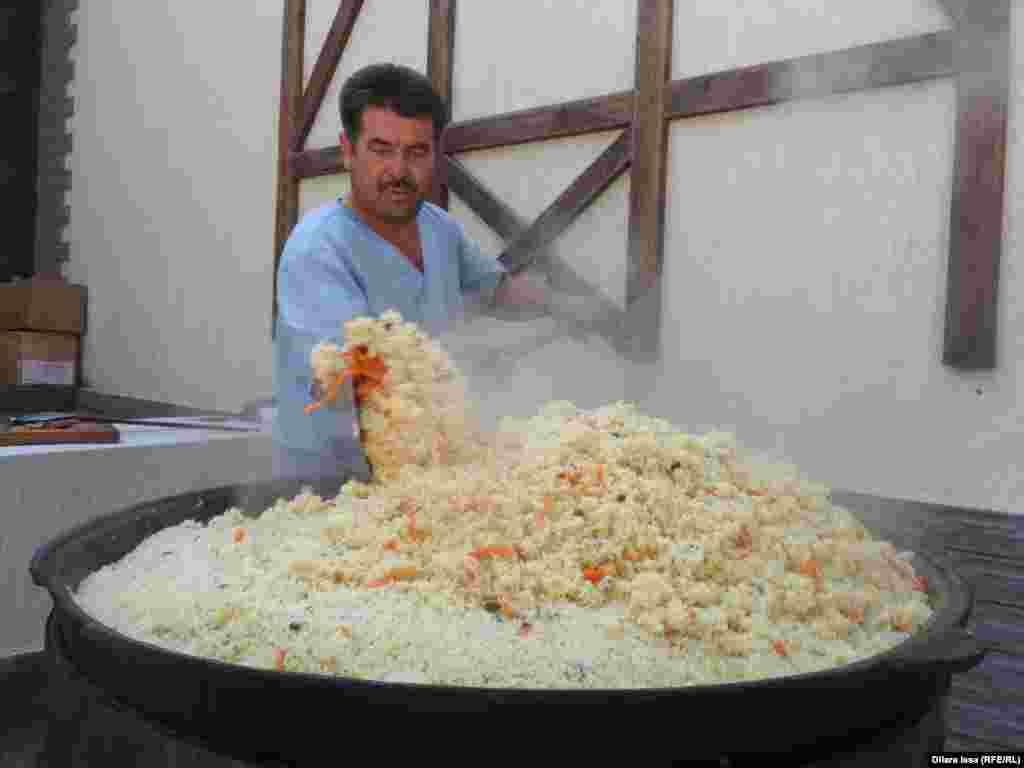 Повар Кайрат Исматуллаев готовит плов в казане емкостью 50 килограммов. Пловом угостили гостей праздника бесплатно.