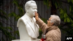 A woman touches a bust of the late Yugoslav and Serbian President Slobodan Milosevic at his grave in the town of Pozarevac.