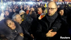 "Ukrainian opposition leader Arseniy Yatsenyuk (right) joins antigovernment protesters in the singing of the Ukrainian national anthem at the ""Euromaidan"" encampment on Independence Square in Kyiv in mid-December."