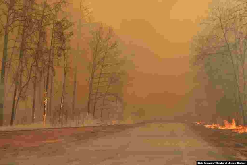 "Smoke and flames gave the forest in the exclusion zone an eerie orange glow on April 10. Officials with Ukraine's Emergency Situations Service said that radiation in the region and in the capital, Kyiv, was within ""permissible"" levels."