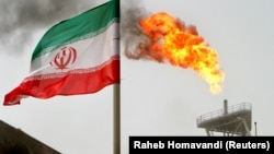 An oil production platform in the Soroush oil fields is seen alongside an Iranian flag in the Persian Gulf.