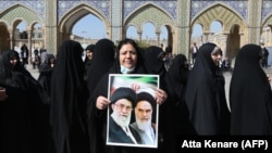 An Iranian woman holds a portrait of former and current Supreme Leaders, Ayatollah Ruhollah Khomeini and Ayatollah Ali Khamenei, at the polling statation at the Shah Abdul Azim shrine in the south of Tehran, February 21, 2020.