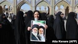 Женщина держит портреты бывшего и нынешнего духовных лидеров — аятоллы Рухоллы и аятоллы Али Хаменеи — во время очереди на голосование 21 февраля на юге Тегерана.