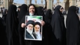 A woman holds a portrait of former and current supreme leaders, Ayatollah Ruhollah Khomeini and Ayatollah Ali Khamenei, as she queues up to vote on February 21 at the Shah Abdul Azim shrine on the southern outskirts of Tehran.