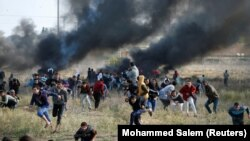 "Palestinian protesters run for cover during clashes with Israeli troops as Palestinians call for a ""day of rage"" in response to U.S. President's recognition of Jerusalem as Israel's capital."