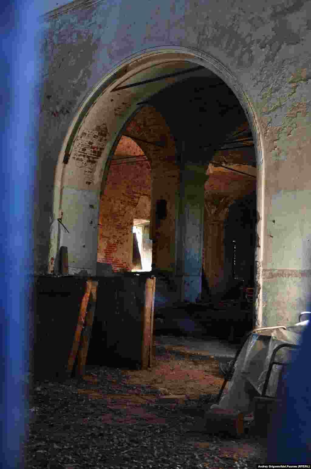 Внутрь не попасть, но сквозь зазор в воротах можно рассмотреть детали интерьера. Говорят, при советской власти внутри устроили склад удобрений.