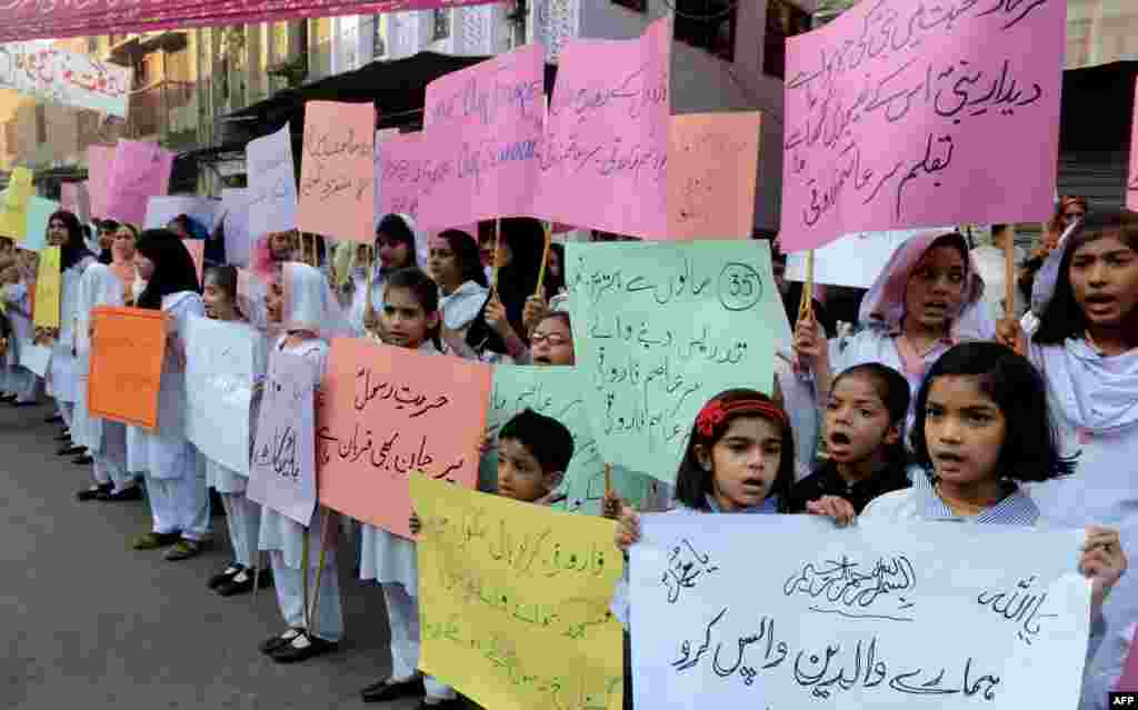 Students of Farooqi Girls' High School wave placards as they stage a protest in Lahore on November 3, demanding the reopening of their school after it was set on fire by an angry mob that alleged the school gave a test that insulted the Prophet Muhammad.