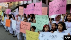 Pakistani students of Farooqi Girls' High School wave placards as they stage a protest in Lahore on November 3, demanding the reopening of their school after it was set on fire by an angry mob.