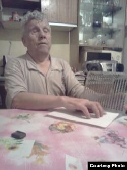 Виктор Тысяцкий Брайль әліпбиімен жазылған мәтінді оқып отыр.