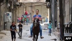 کودکان در حال بازی در خیابان ها حلب که در کنترل گروه های مخالف است.