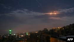 A picture taken early on January 21, 2019 shows Syrian air defense batteries responding to what the Syrian state media said were Israeli missiles targeting Damascus.