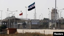 Turkey -- Turkish (L) and Syrian Independence flags are seen between the border gates Akcakale of Turkey and Tel Abyad of Syria, in Akcakale, southern Sanliurfa province, 04Oct2012