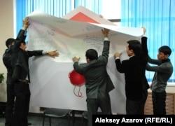 Молодежные активисты вкладывают лист ватмана с поздравлениями Назарбаеву в гигантский конверт размером полтора на два метра. Алматы, 29 ноября 2012 года.