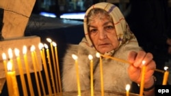 A woman lights candles at a cathedral in Sarajevo, capital of Muslim-majority Bosnia. Ethnic and religious divides remain sensitive issues in the country.
