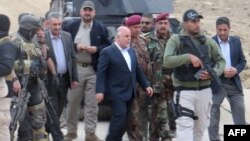 Iraqi Prime Minister Haider al-Abadi (center) visits Ramadi on December 29 after the city had been retaken from Islamic State extremists.