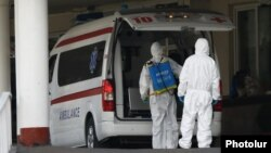 Armenia -- Workers disinfect an ambulance outside Surp Girgor Lusavorich hospital in Yerevan, April 8, 2020.