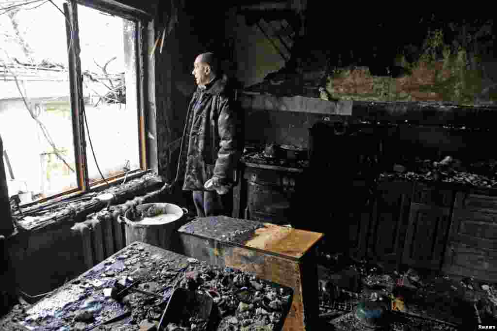 A local resident looks out of a window in his house, which was damaged by shelling in the rebel-held city of Donetsk. (Reuters/Alexander Ermochenko)