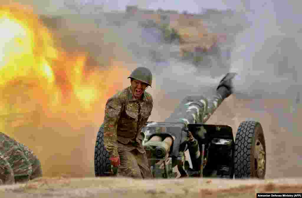 An ethnic Armenian soldier in the separatist Karabakh forces fires an artillery piece toward Azerbaijani positions during fighting over the breakaway Nagorno-Karabakh region on September 28. ( AFP/Armenian Defense Ministry)