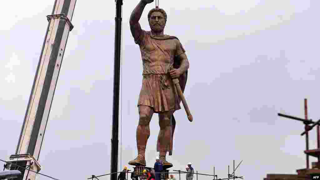 A crane lifts a 13-meter-high bronze statue of Philip II of Macedon, the father of Alexander the Great, onto a 15-meter-high pedestal in central Skopje.