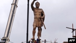 "A crane lifts a 13-meter-high bronze statue of Philip II of Macedonia, officially named ""The Warrior,"" onto its 18-meter-high pedestal in central Skopje on May 22."