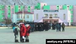 Группа девочек стоит на площади, на которой собрались полицейские. Город Жанаозен, 14 декабря 2013 года.