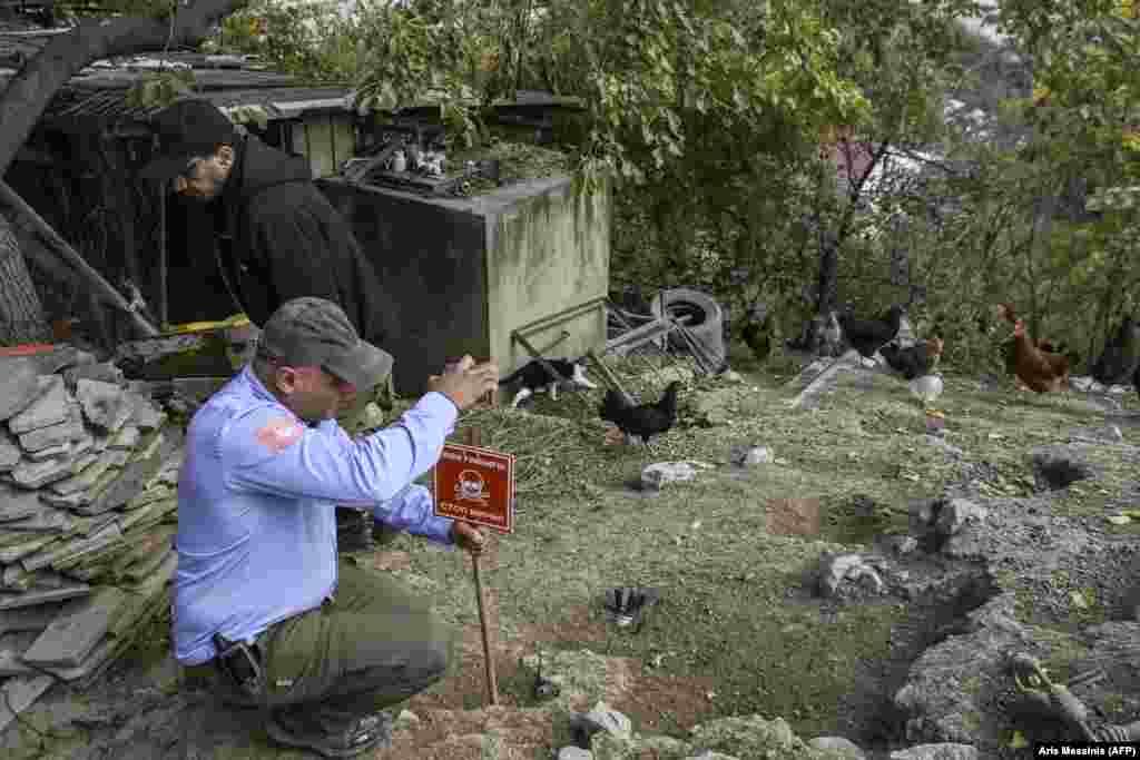 Член неправительственной организации, занимающейся разминированием, устанавливает во дворе Степанакерта табличку с предупреждением о неразорвавшемся снаряде. 14 октября 2020 года.